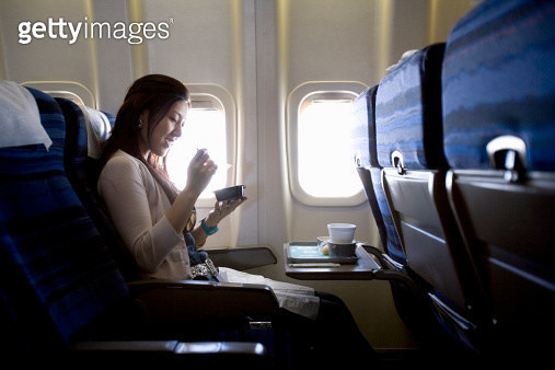 Woman eating meal in airplane - gettyimageskorea