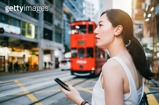 Young woman using smartphone application to navigate direction in busy downtown city street - gettyimageskorea
