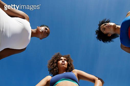 Confident athletes in sportswear looking away against blue sky - gettyimageskorea