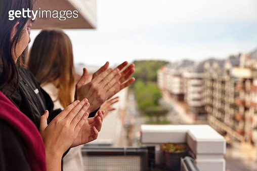 Family applauding from the balcony of their home - gettyimageskorea