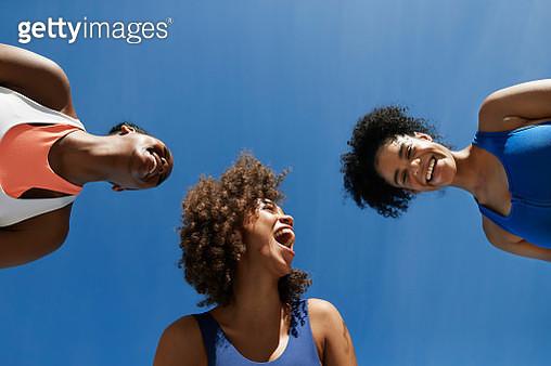 Cheerful female athletes in sportswear against blue sky - gettyimageskorea