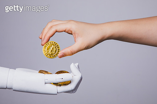 human hand taking bitcoin from robotic hand - gettyimageskorea