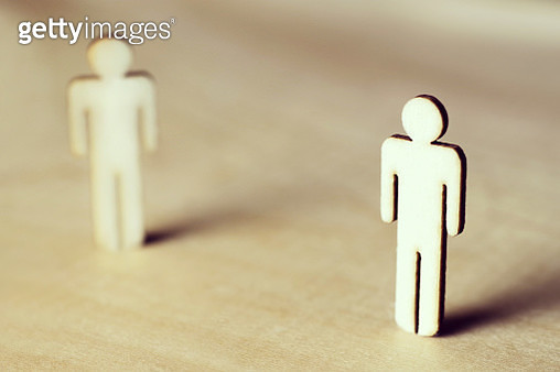 Two male wood cutouts standing apart - gettyimageskorea