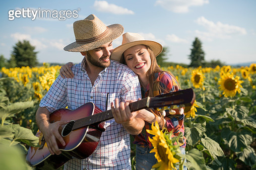 Young man playing the guitar, standing with his girlfriend in the field of sunflowers in bloom. - gettyimageskorea