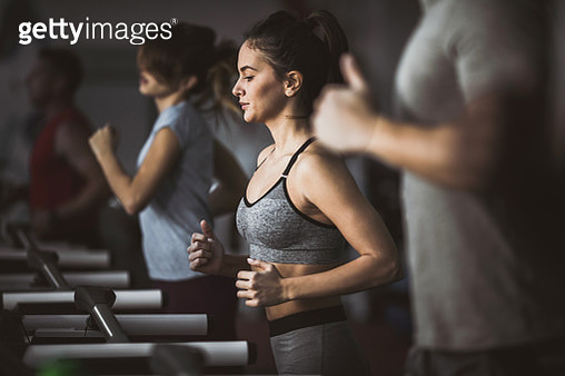 Group of young athletes warming up on treadmills in a gym. Focus is on woman. - gettyimageskorea