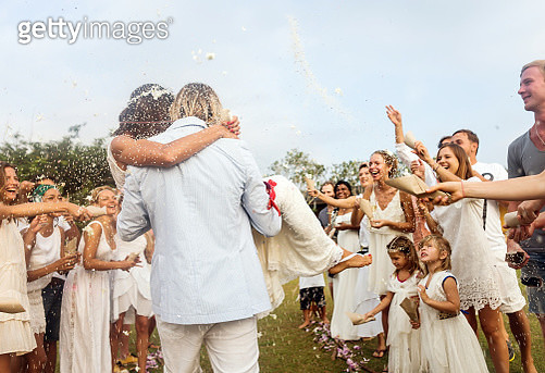 Wedding guests tossing rice at newlyweds, outdoors - gettyimageskorea