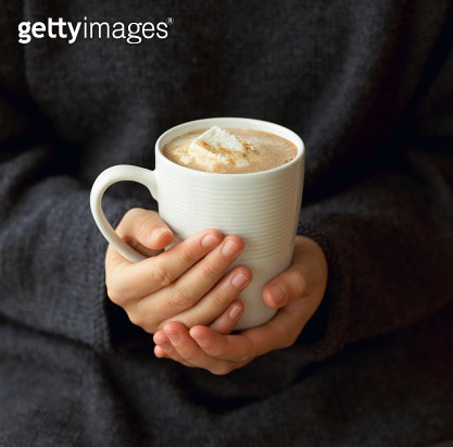 Woman holding mug of hot chocolate with melted marshmallows, mid section, close-up - gettyimageskorea