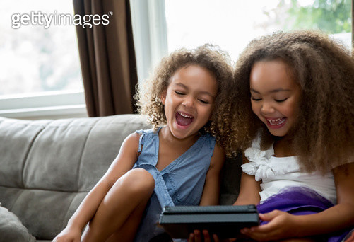 Mixed race girls using digital tablet on sofa - gettyimageskorea