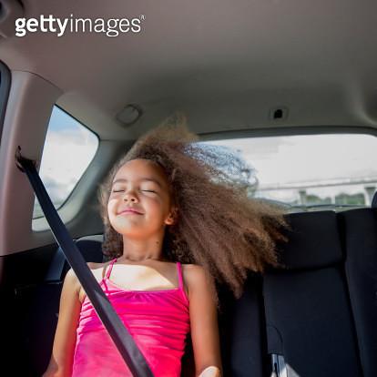 Mixed race girl enjoying wind in hair in back seat of car - gettyimageskorea