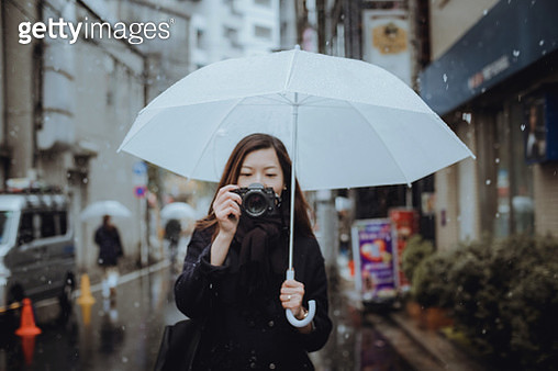 Female traveller carrying umbrella photographing through camera during snowfall in Tokyo, Japan - gettyimageskorea