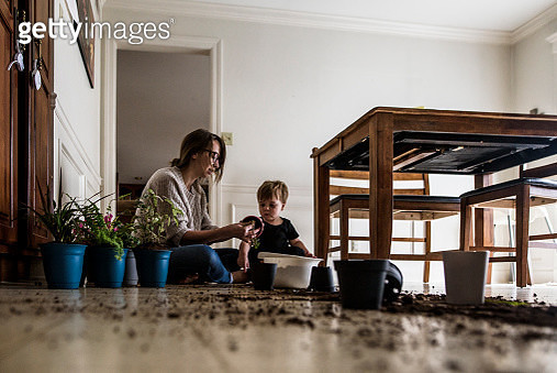 Mother and young son sit on kitchen floor with plants and dirt - gettyimageskorea