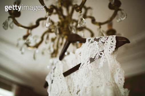 Beautiful lace wedding dress hanging on chandelier - gettyimageskorea