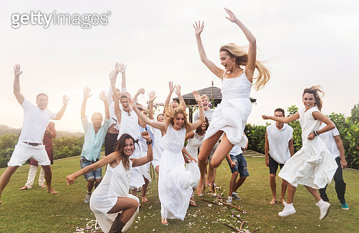 Newlywed couple and guests jumping, outdoors - gettyimageskorea