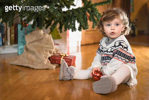 Young baby decorating the Christmas tree at home. She's looking at camera and keeps a Christmas tree ornament in her hands - gettyimageskorea