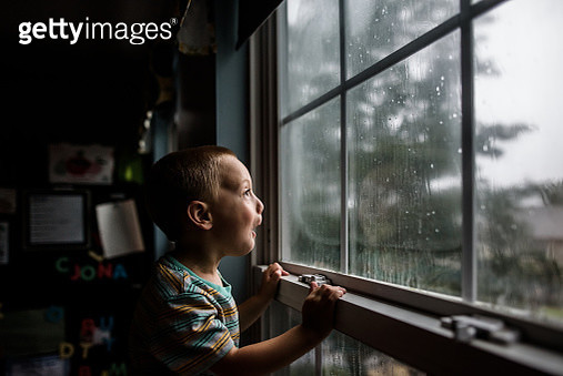 excited boy looking out a window with raindrops at a stormy sky - gettyimageskorea