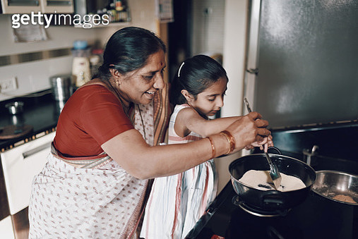 Young girl helping her grandmother while working in the kitchen - gettyimageskorea