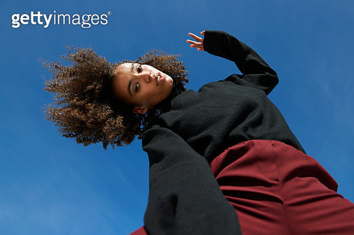 Portrait of young woman with curly hair and head cocked standing against blue sky on sunny day - gettyimageskorea