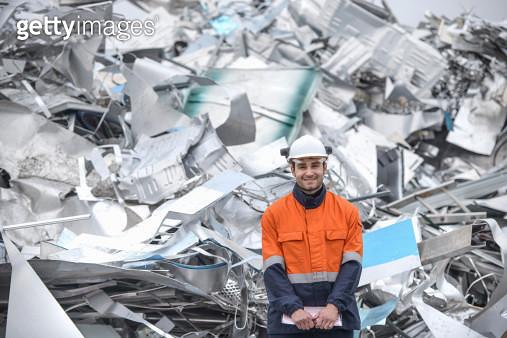 Portrait of worker standing in front of scrap in aluminium recycling plant - gettyimageskorea