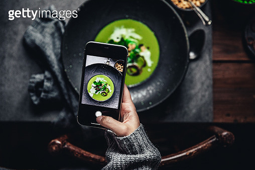 Woman taking a picture of green peas and cream soup - gettyimageskorea