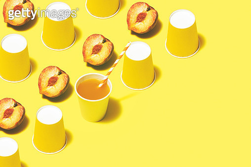 Disposable paper cups on color background. Peach juice and yellow paper cups flat lay on yellow background. - gettyimageskorea