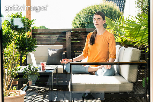 Young woman sitting on couch on terrace practicing yoga - gettyimageskorea