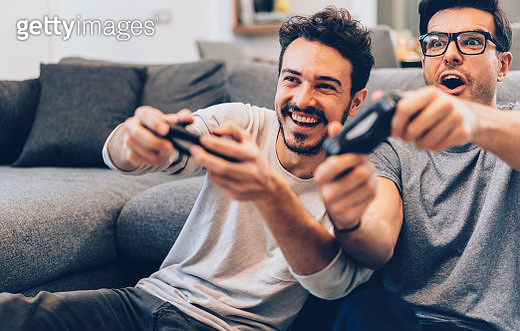 Excited friends playing video games at home - gettyimageskorea