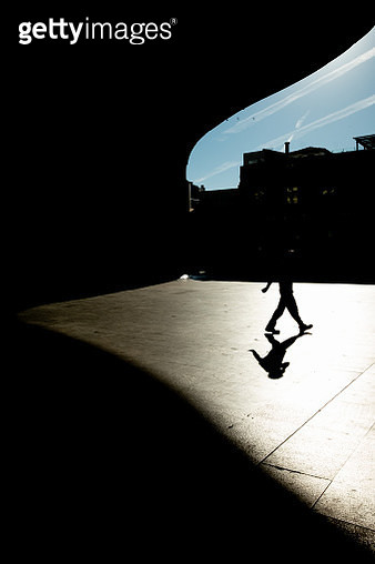 Silhouette Man Walking In City - gettyimageskorea