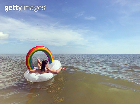 Young girl floating in an inner tube in the ocean. - gettyimageskorea