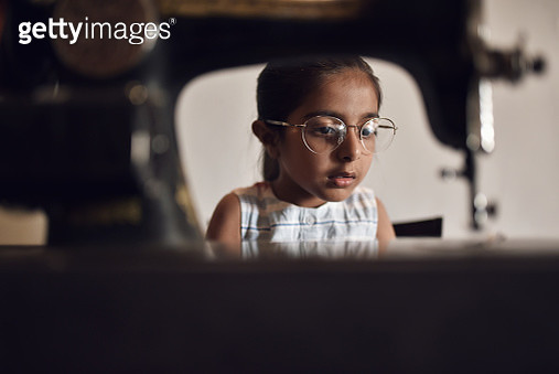 Young girl working on sewing machine wearing her Grandmother's eyeglasses - gettyimageskorea