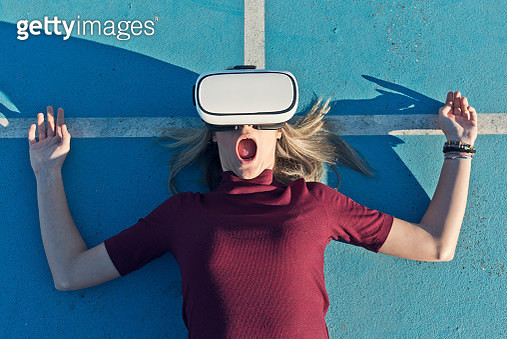 Young woman lying on tennis court wearing Virtual Reality Glasses outdoors - gettyimageskorea