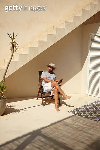 Mature adult uses phone on holiday - gettyimageskorea