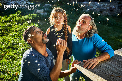 Two men and girl blowing blowball in garden - gettyimageskorea