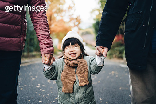 An adorable and happy little girl holding her grandparent's hand and having a relaxing walk in the park - gettyimageskorea