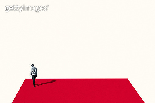 Rear view of sad young man walking on red ramp - gettyimageskorea