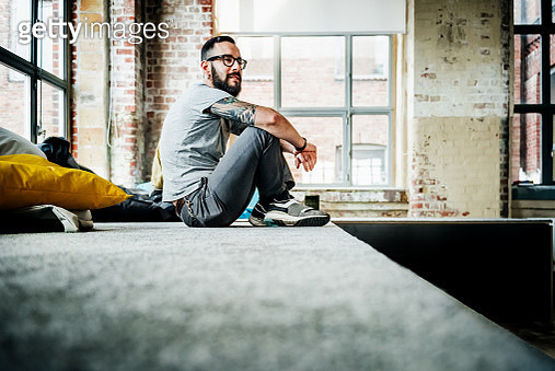 Casual business person sitting in office loft - gettyimageskorea
