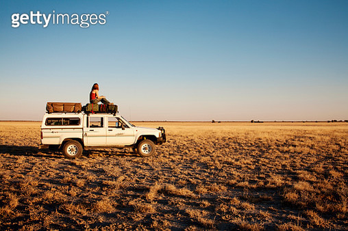Side view of woman sitting on off-road vehicle at field - gettyimageskorea