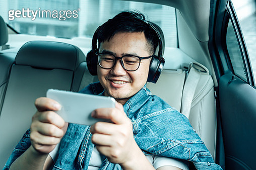 a young male play mobile game  in the car - gettyimageskorea