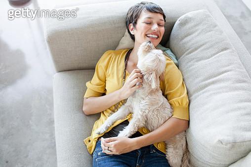 Young woman hugging dog on living room sofa - gettyimageskorea