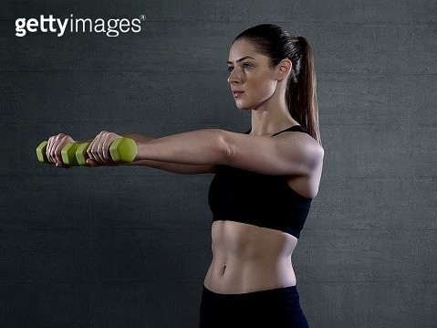 Woman holding hand weights - gettyimageskorea