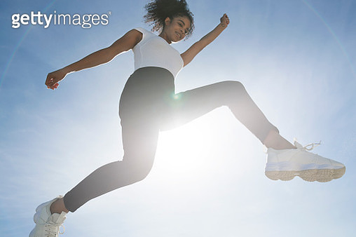 Carefree woman jumping against blue sky on sunny day - gettyimageskorea