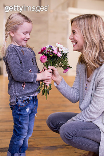 Young girl giving mother bunch of flowers - gettyimageskorea