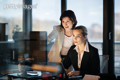 Young and Mature Business Woman Working Late - gettyimageskorea