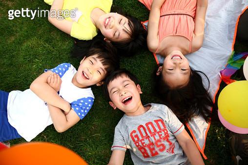 Children lying on the grass. - gettyimageskorea