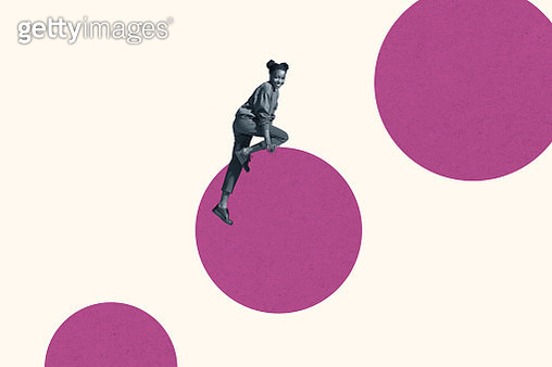 Smiling young woman climbing on magenta circle - gettyimageskorea