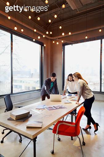 Colleagues looking at laptop in design studio - gettyimageskorea