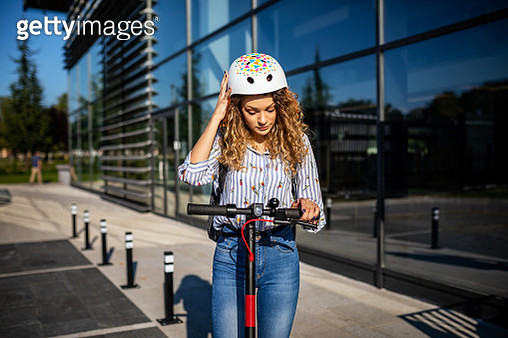 Modern young business woman prepares to ride electric scooter - gettyimageskorea