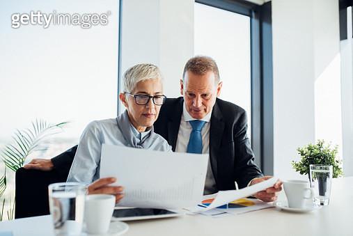 Business people revising paperwork - gettyimageskorea