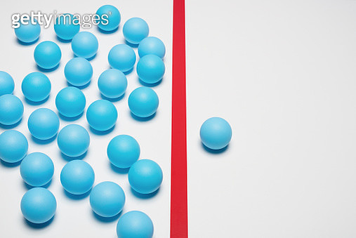 One blue ball on one right side of red line, many blue balls on left side - gettyimageskorea