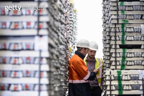Workers inspecting stacks of aluminium ingots in warehouse - gettyimageskorea