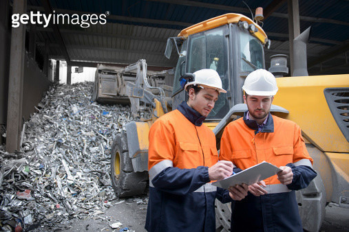 Workers inspecting paperwork in  recycling plant in front of scrap aluminium - gettyimageskorea